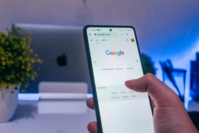 Mano con smartphone navegando en Google