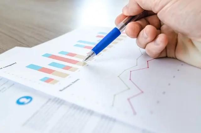 Una mano con un bolígrafo analizando datos estadísticos