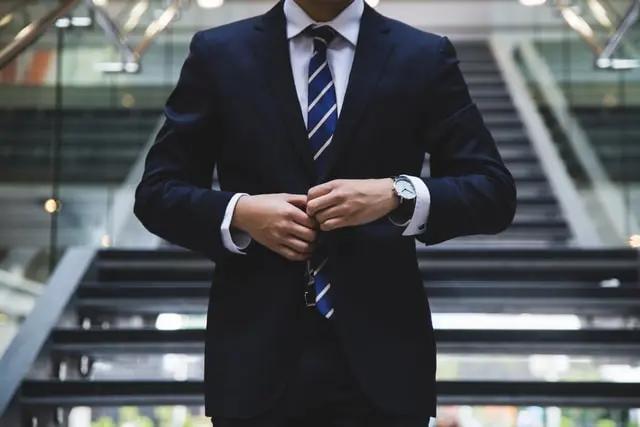 Hombre abotonándose el saco de su traje