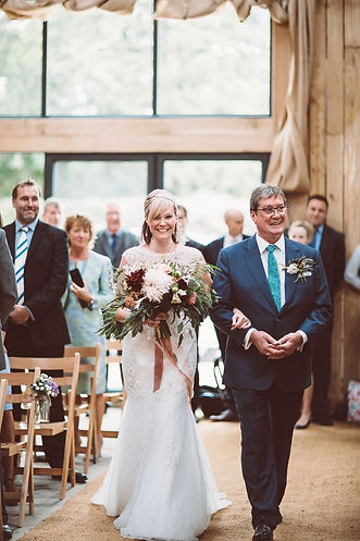Bride being walked down the isle in th  ceremony barn at Chafford Park Estate