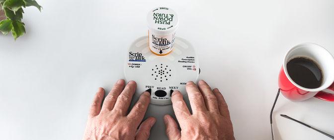 Hands on a ScripTalk Talking Prescription reader with medication