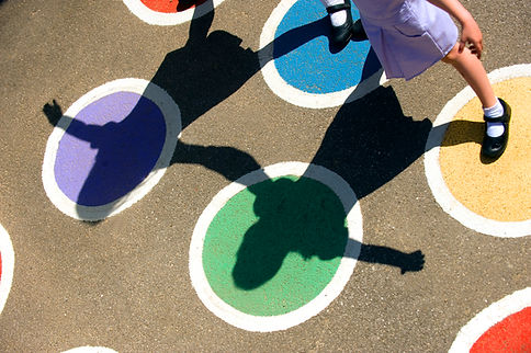 Four painted circles on a concrete playground, purple, green blue and yellow respectively, outlined in white. The shadow of two young girls holding hands and playing hopscotch can be seen on the concrete. In the corner one of the girls' legs is glimpsed, she is wearing a classic black t barred shoe with white ankle socks.