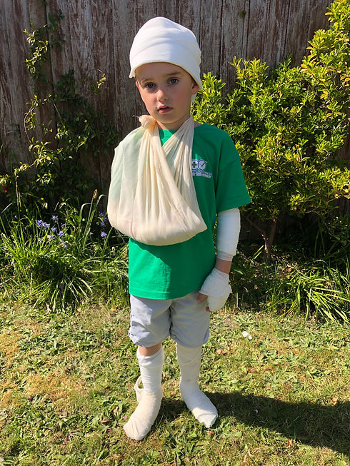 A boy aged around 9-10 stands outside. He is wearing a green t shirt with Trustworthy Services branding on and denim shorts. The top of his head is bandaged, as well as his left forearm, hand and both lower legs. His right arm is in a sling. He looks moodily at the camera. Behind him is a flowerbed and fence.