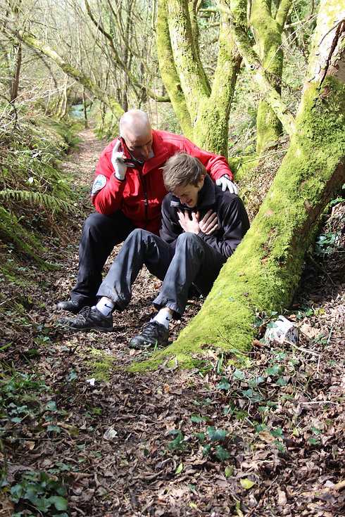 A first aider in a red jacket supports a young man in dark clothing outside on a forest path lined with autumn leaves. The young man is sitting on the ground by a mossy tree trunk clutching his chest. He looks distressed. The first aider is next to the man, making an emergency phone call and he has his hand on the man's shoulder.