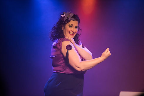 """Vie Portland is on stage, mid shot, standing sideways, her profile facing to the right. She is grinning widely at the camera. Her curly dark hair frames her face and is at shoulder length. She has a purple bow in her hair, gold eye makeup and is wearing red lipstick and a shiny, purple sleeveless blouse. She is making a """"strong"""" pose with her right arm- showing purple tassles stuck to her biceps."""