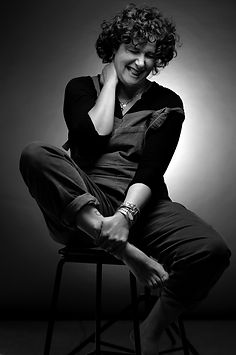 Black and white picture of a laughing woman with thick, curly shoulder length hair.  The lady is wearing dungarees over a black blouse and the left shoulder strap of her dungarees has dropped down her arm. Her right hand is resting on her neck, with her left gripping her lower right leg, so her whole body is at an angle. She has a watch and heavy bangle on her left wrist and her chain necklace pendant catches the light.