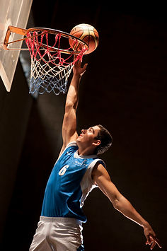 A young black man reaches for a slam dunk, with a white and orange striped basketball inches from a red white and blue roped ring. He is wearing a royal blue sleeveless sports shirt with a white 6 emblazoned on the front.