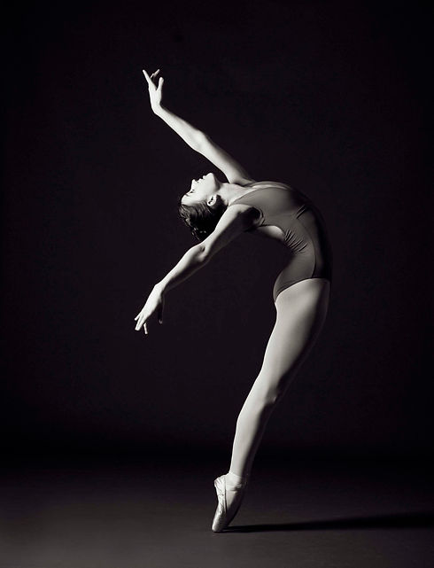 A black and white portrait of a female ballet dancer in profile. She stretches backwards, her right arm behind her and her left reaching upwards, with carefully pointed fingers.  She is looking up, her body curves gracefully to the right. The light highlights her sharply pointed toes and fingers.