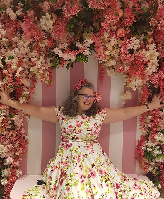 A picture of our founder, Vie Portland, sitting against stripey pink and white wallpaper and flanked by a range of pink and white flowers, roses and lillies above her head. Vie is wearing a white dress with pink flowers on to compliment the background and is holding out her arms exuberantly, a big grin on her face. Her hair is shoulder length grey brown and elegantly curly. She has pink flowers in her hair. She is wearing glasses and looks jolly and welcoming.