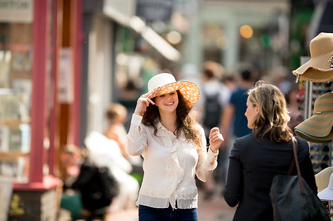 A young lady with dark shoulder length hair stands in the middle of a street market. She is grinning to another lady in black, who has her back to the camera,  as she tries on a large, white wide brimmed hat.  In the background there are people walking up and down the street and to her left a shop front with pink window frames.