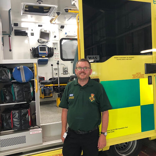 Paul Lailey standing in front of an ambulance. He is wearing a dark green polo shirt and dark trousers. He has short dark hair, a moustache and beard. He is wearing square shaped glasses. The door of the ambulance is open and we can see all the equipment inside. The ambulance side is painted yellow and it has neon yellow and green checks on the doors.