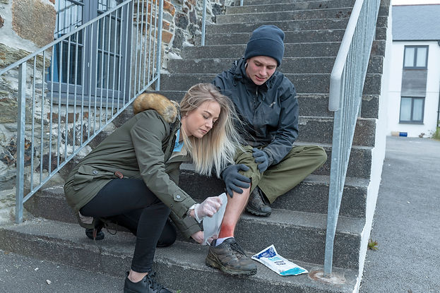 A young blonde lady in a khaki parka attends to a man's ankle. It looks as if he has fallen down the stairs, as he is sitting halfway up them. They are concrete, outdoor steps leading from a building and bordered by metal handrails. He is holding his leg with gloved hands.  He is wearing khaki trousers and a navy wax jacket.