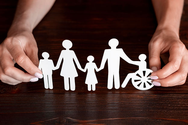 A pair of hands hold a paper cutout depicting a family group of a man, woman, son, daughter and a sibling in a wheelchair. All are linked.