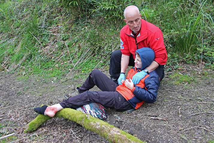 A first aider wearing a red jumper. He is outdoors attending to a young boy who appears to have fallen. The main is wearing blue surgical gloves and is supporting the boy, holding his right hand and appearing to try to help him up. The boy has his right leg slightly raised. The boy is grimacing in pain. He has a red and navy puffer jacket on with its hood up and dark trousers, which are stained with mud. He has fallen on a path bordered by a wildflower bank.