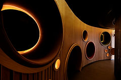 University of Winchester West Downs campus interior, timber clad corridor with portholes of different sizes, mimicking the shape of musical speakers.