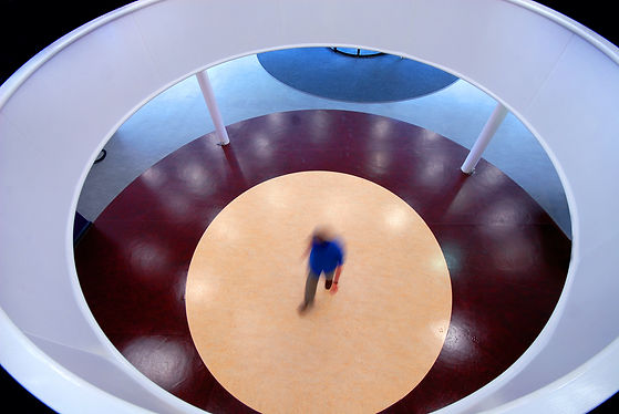 We are looking down through the top of a circular atrium into the corridor below. The lino flooring has large pale circles on, one inside another, looking similar to an eye.  The central colour is beige or sandy brown, the outer circle is burgundy with the furthest away a duck egg blue.  There is a man in a royal blue t shirt and grey trousers walking through the centre of the picture at speed- he is slightly blurred. The picture is framed by the white circular structure of the upper floor.