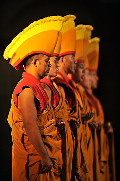 A line of Buddhist monks stand in profile in red and terracotta robes. The elaborate folds in their clothes are illuminated by deep shadows, and their ceremonial orange hats have bright red bias taped edging and bright yellow tassled fringing on the top.
