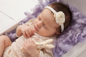 Baby girl holding a white bunny on lilac curly wool stuffer and in wooden bed.jpg