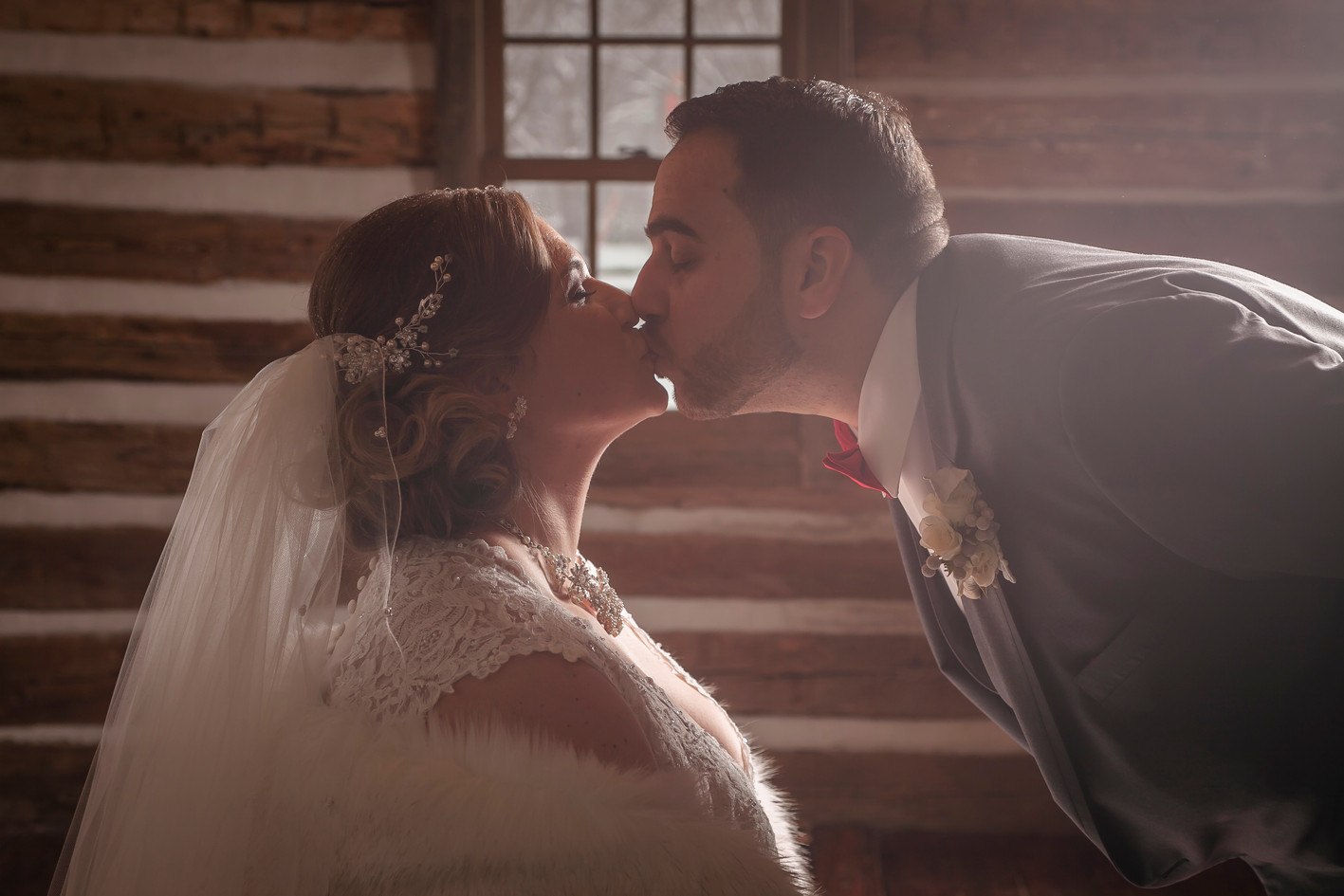 Husband and wife share a kiss in an old cabin with sunlight shining through.