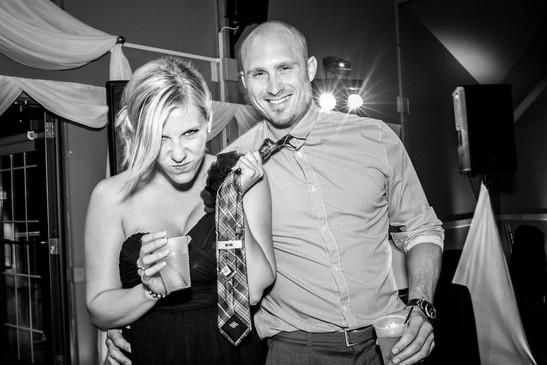 women holding boyfriends tie at a wedding party