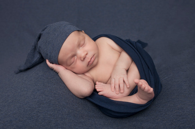 Newborn Boy wearing a blue touque and wrapped in denim blue wrap.jpg
