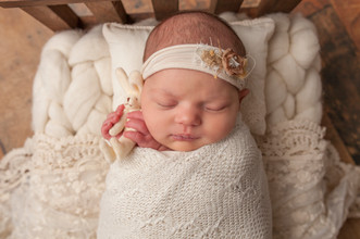 Newborn baby girl holding easter bunny in wooden bed