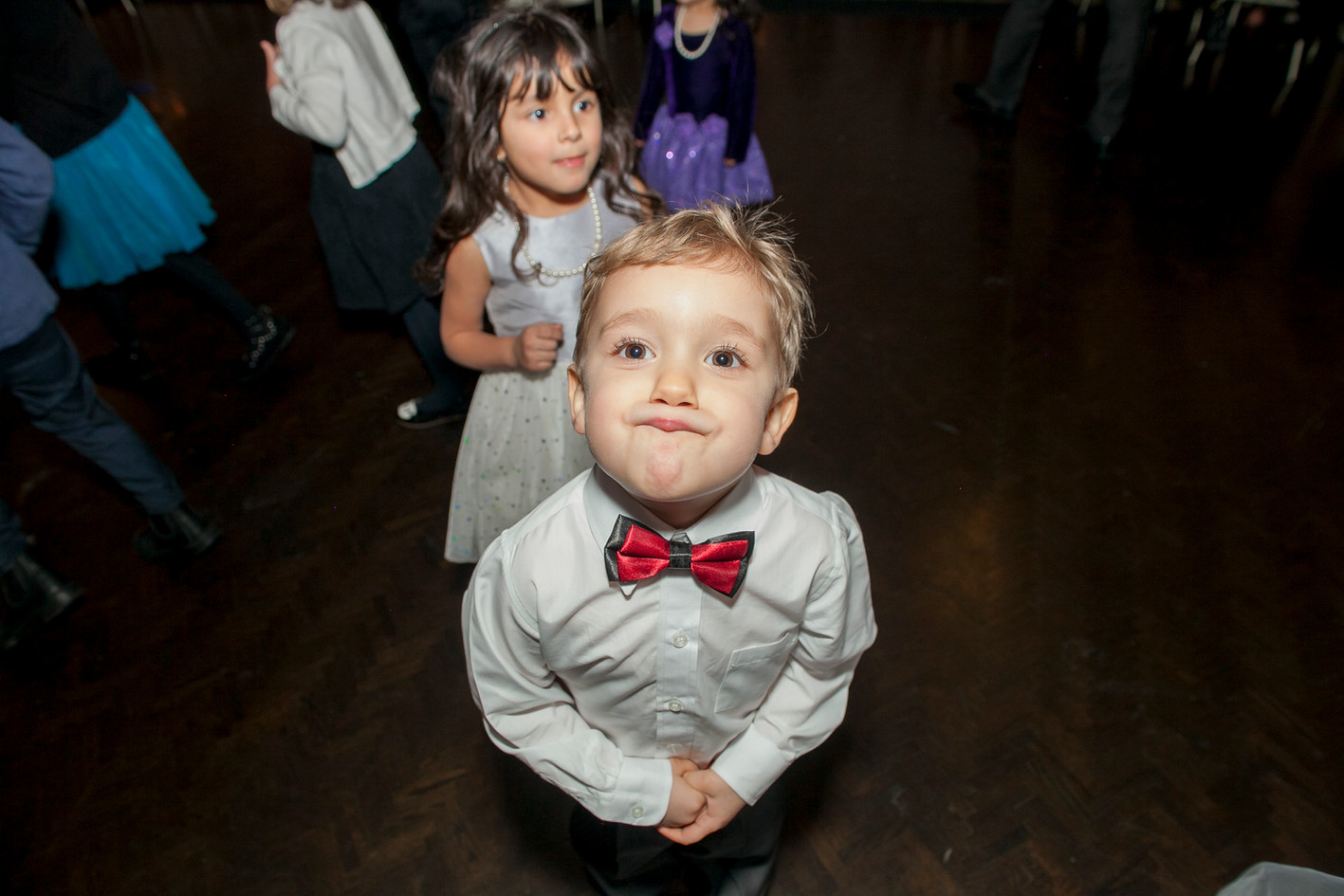 Little boy wearing a red bowtie at a wedding party