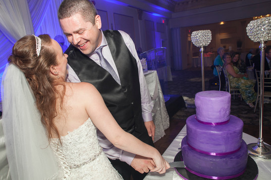 Bride and groom cutting a purple three tier wedding cake at a wedding party.