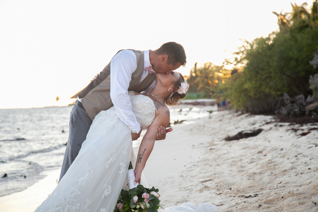 Bride and Groom kiss on a Mexico beach. Destination wedding.