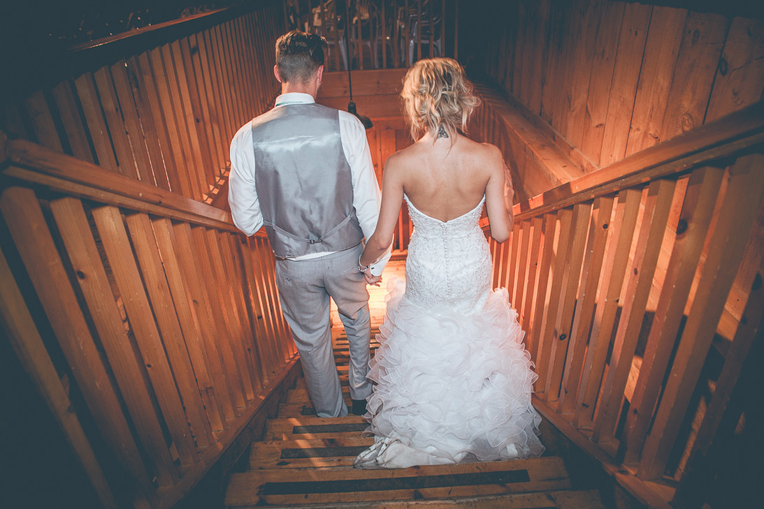 Newly wed couple holding hands walking down the stairs.