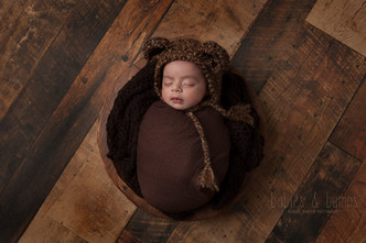 newborn in brown bear hat wrapped in brown wrap.jpg