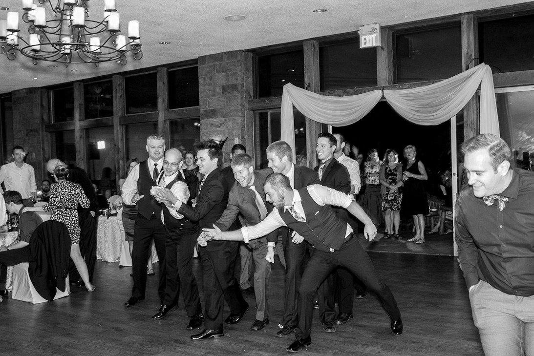 Guys are reaching out for the garter toss at a wedding party.