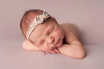 Newborn baby girl with head on hands pose.jpg