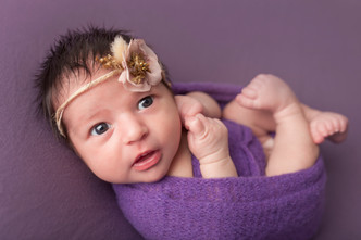 baby girl in huck finn pose with purple wrap and background.jpg