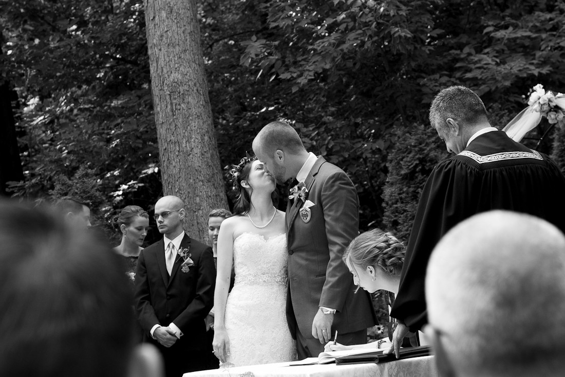 Wedding ceremony outdoors in a park with married couple kissing.