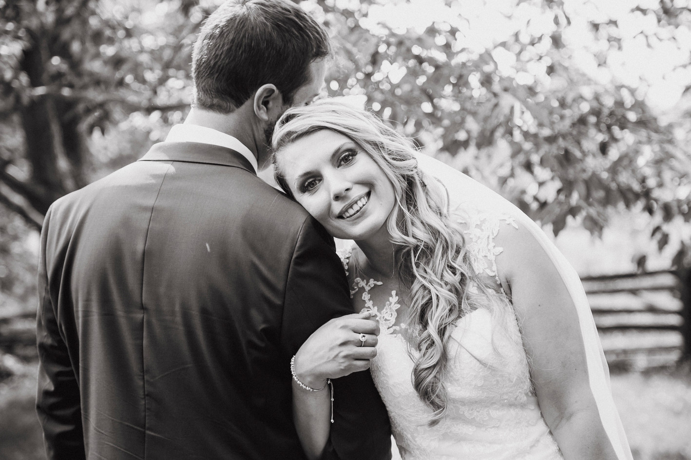 Bride smiling and holding grooms arm posing for wedding photo.