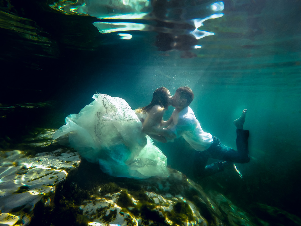 Under water wedding image of married couple kissing under water. Bride wearing wedding dress. Fairy Tale Mexico destination wedding with trash the dress.