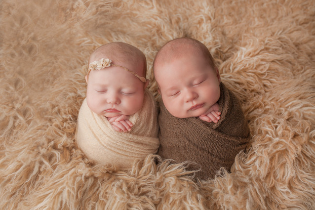newborn baby twins wrapped in beige and brown wraps potato sack pose