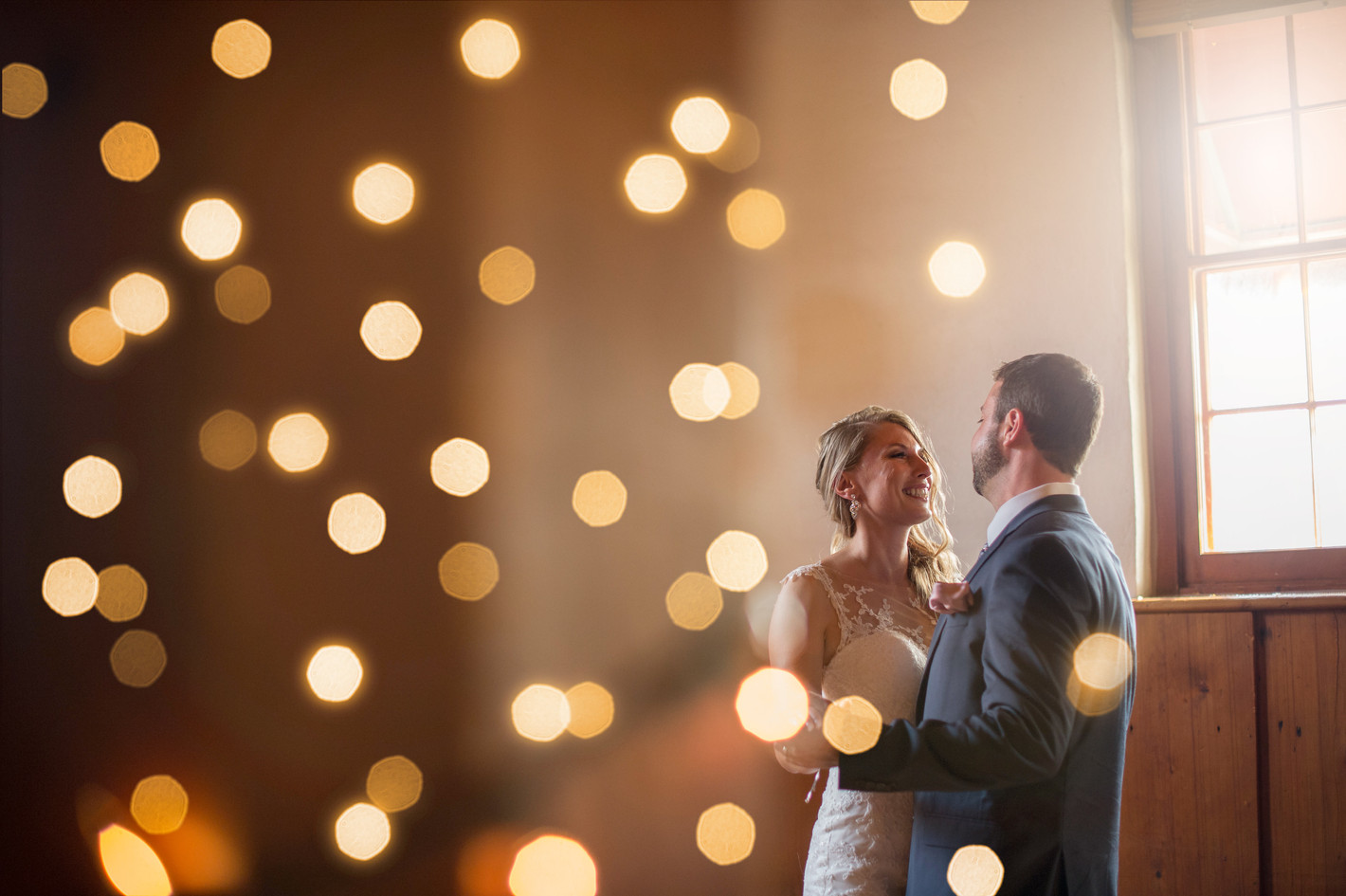 Newly married couple dancing by twinkle lights on their wedding day