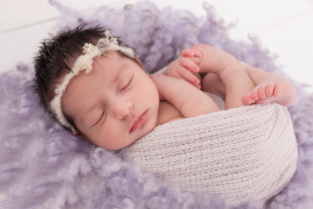 Newborn baby girl in lilac fur stuffer and lilac wrap.jpg