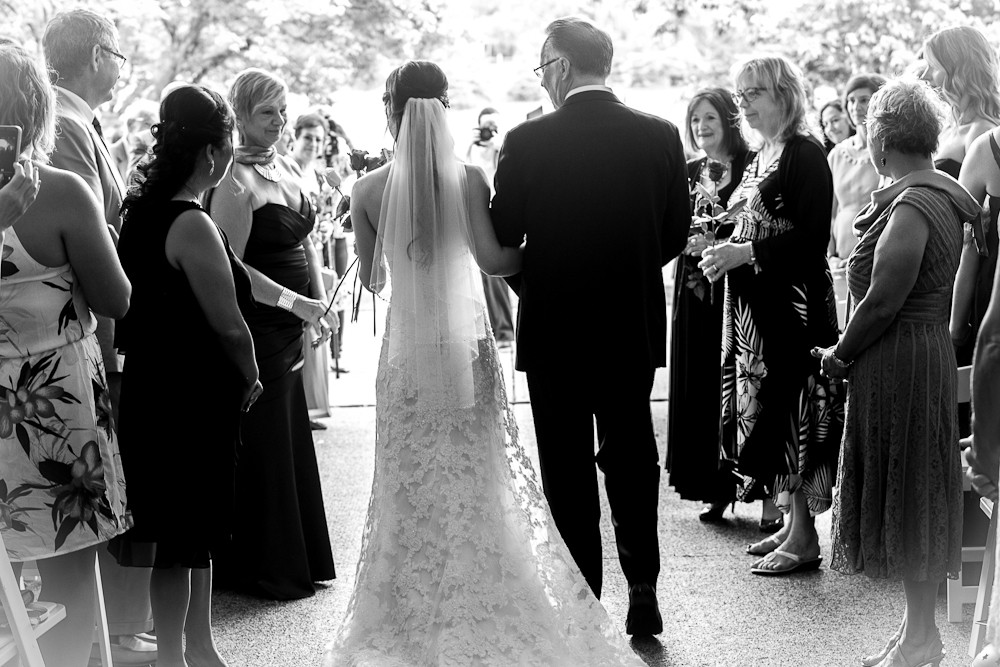 Bride walks down isle with father in arms. Black and white wedding ceremony image.