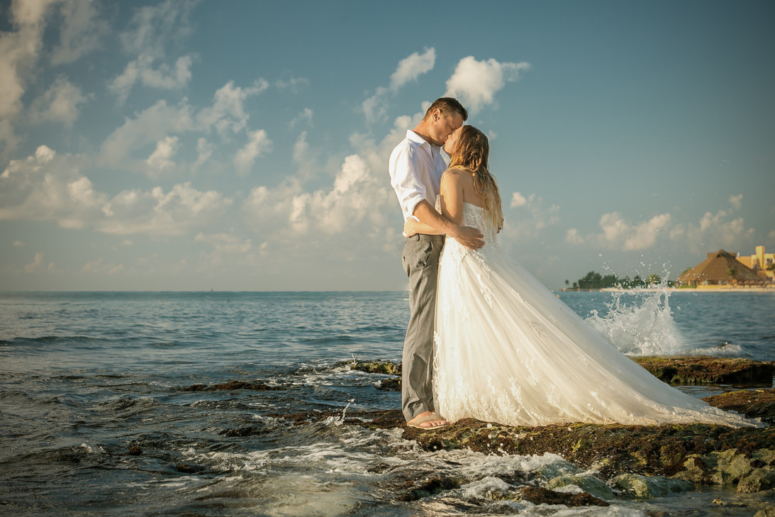 Married couple kiss on a beach. Bride wearing her wedding dress. Trash the dress in Mexico destination wedding.