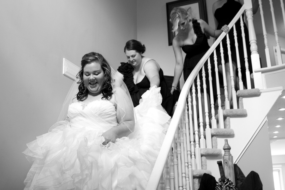 Bride walks down the stairs with brides maids holding wedding dress.