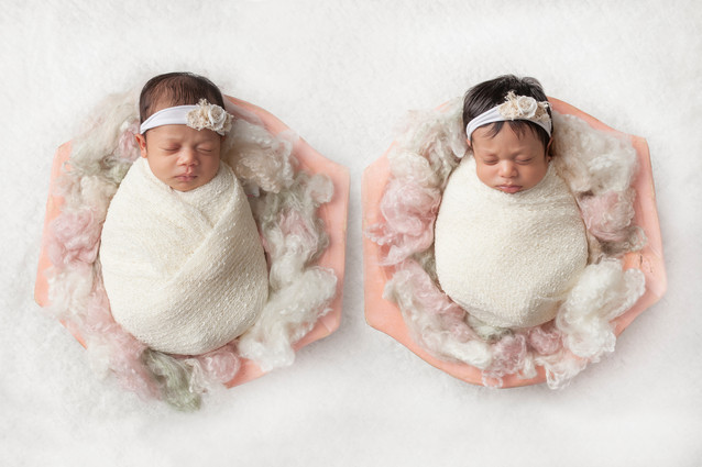 Twin newborn girls wrapped in white in pink wooden bowls.jpg