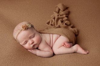 Newborn baby girl on brown background with wrap