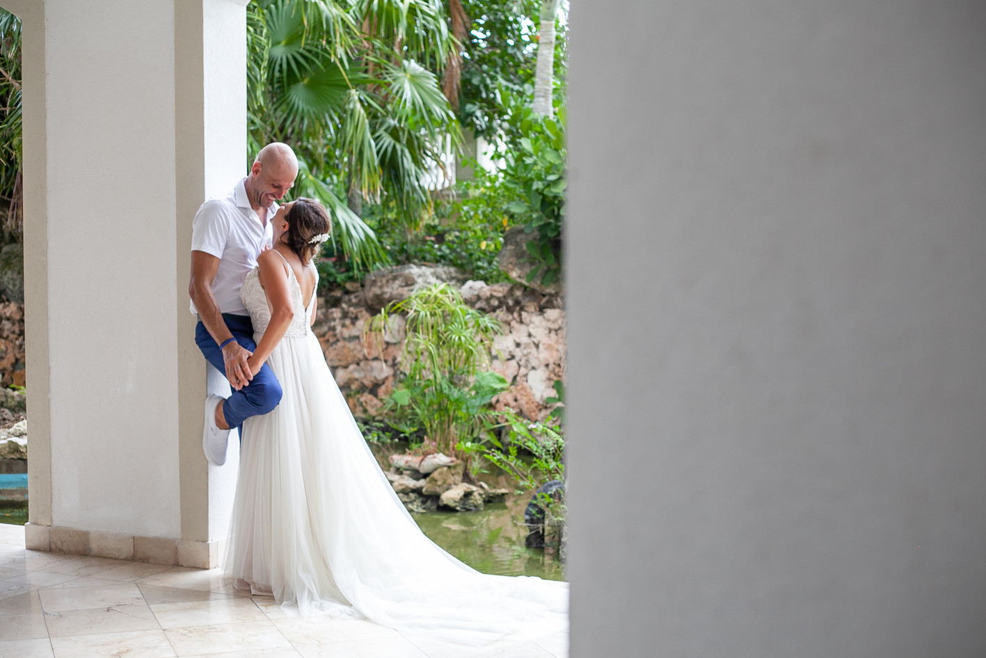 Husband and Wife married couple hold hands at a Cuba resort hallway. Couple staring into each others eyes.