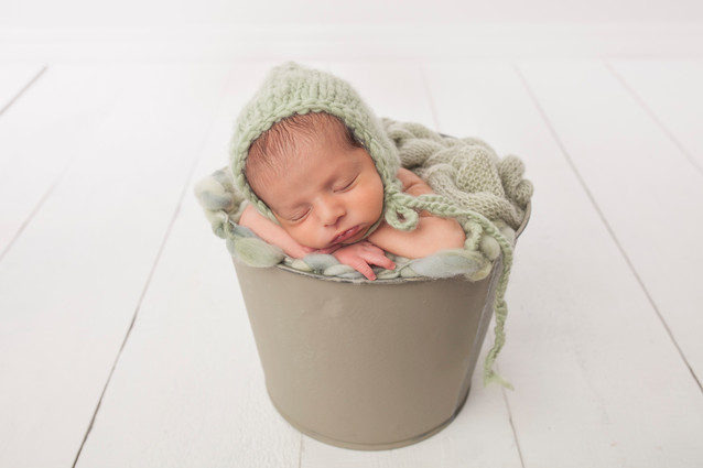 Newborn baby boy in bucket pose with green wraps