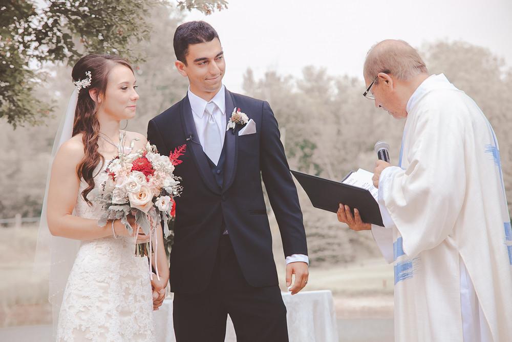 Bride and Groom outdoor wedding ceremony holding bouquet.