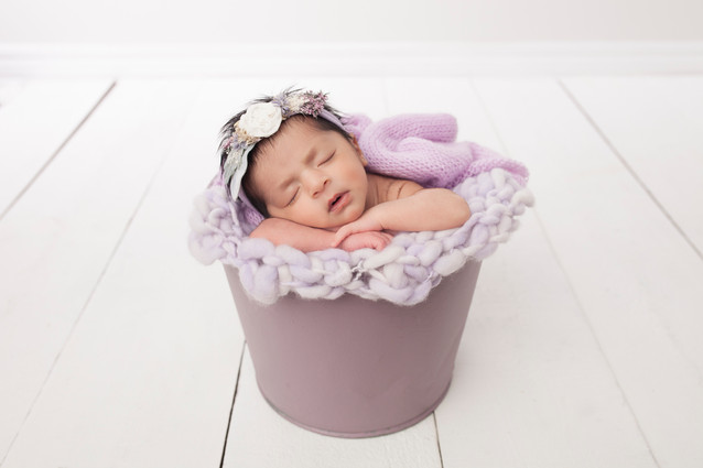 Newborn baby girl in bucket pose with purple wraps and bucket