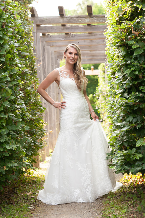 Bride standing in a vineyard in her wedding dress.